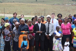 CBF field personnel Mark and Sara Williams (top left) and Second Memphis pastor Stephen Cook (top right) gather with members of a church in Emmaus, South Africa, to pray at the spot where the community discovered water and prepared to dig a well.