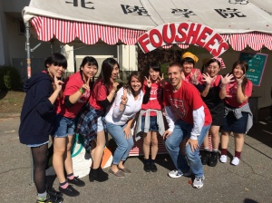 Carson and Laura Foushee pose during the Hokuriku Gakuin University fall festival with the college students in the English Club they lead. The club's booth for the festival was a chili hot dog booth named after the couple.