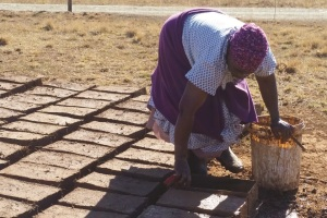 A woman makes bricks for a tuck shop, a small store where she can sell essential items to her neighbors, in a rural village in the Drakensberg Mountains just outside of Winterton, South Africa. Villagers face extreme poverty and reside in the country's poorest province, where more than one-third of the residents live with HIV.