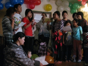 Mary Htoo (in red) sings among other Karen youth at a house blessing in Louisville, Ky.