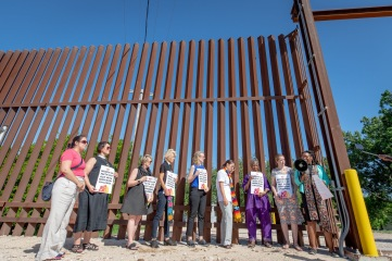 Women faith leaders gather at the border wall to advocate for separated families and leave prayers.